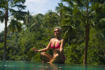 attractive and happy middle aged Asian Indonesian woman in bikini relaxed at infinity pool of exotic resort in tropical jungle sitting in lotus yoga position meditating enjoying exotic holidays Banco de Imagens