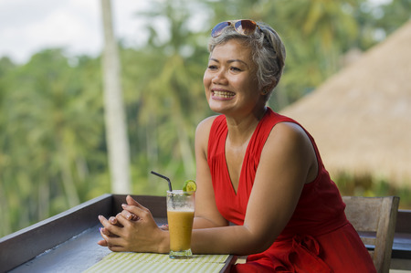 natural lifestyle outdoors portrait of attractive and happy middle aged Asian Indonesian woman in stylish red dress enjoying tropical holiday trip at tourist resort with beautiful jungle view