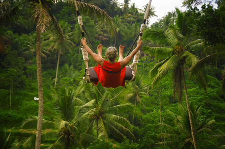 outdoors lifestyle back portrait of attractive happy middle aged woman with grey hair riding rainforest swing carefree swinging and enjoying tropical jungle adventure feeling free and excited