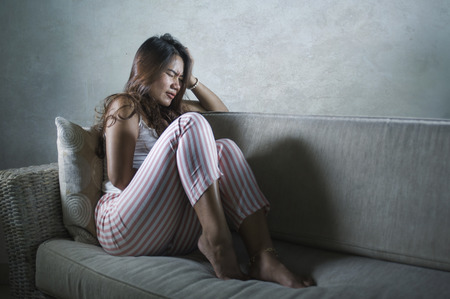 dramatic lifestyle portrait of young sad and depressed Asian Indonesian woman stting at home couch crying frustrated and upset suffering stress and depression after breakup Stockfoto