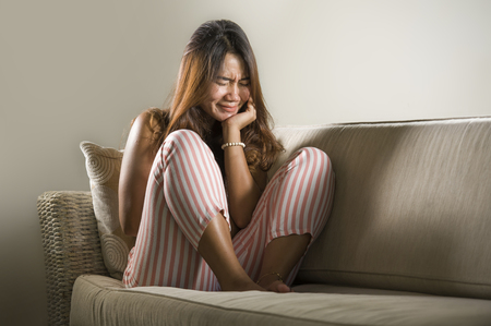 dramatic lifestyle portrait of young sad and depressed Asian Indonesian woman stting at home couch crying frustrated and upset suffering stress and depression after breakup 版權商用圖片