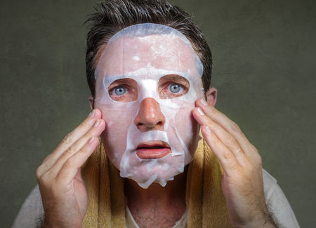 lifestyle isolated background portrait of young weird and funny man at home trying using beauty paper facial mask cleansing learning anti aging treatment in concentrated face expression