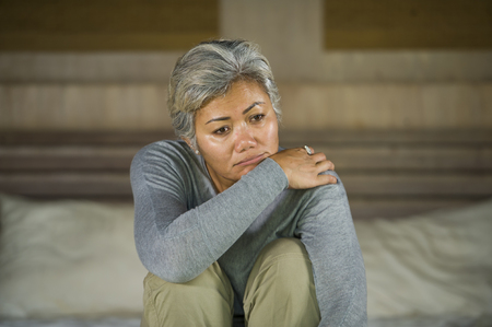 desperate 40s - 50s mature lady, dramatic lifestyle home portrait of attractive sad and depressed middle aged woman with grey hair on bed feeling upset suffering depression and anxiety Stock fotó