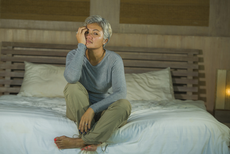Depressed 40s - 50s mature female, dramatic lifestyle home portrait of attractive sad and lost middle aged woman with grey hair sitting on bed feeling frustrated suffering depression and pain