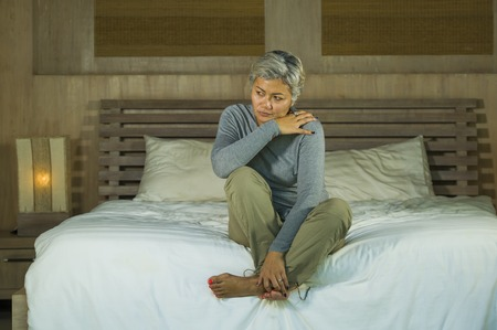 desperate 40s - 50s mature lady, dramatic lifestyle home portrait of attractive sad and depressed middle aged woman with grey hair on bed feeling upset suffering depression and anxiety