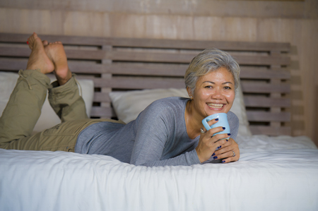 home portrait of attractive and successful mature woman with grey hair sitting on bed drinking coffee relaxed smiling happy and charming as middle aged female enjoying domestic lifestyle