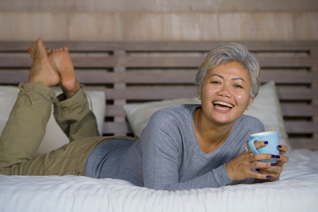 home portrait of attractive and successful mature Asian American woman with grey hair sitting on bed drinking coffee relaxed smiling happy as middle aged female enjoying domestic lifestyle