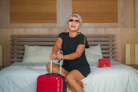 travel bliss and weekend getaway excitement. Attractive and happy mature Asian woman smiling cheerful arriving at hotel room sitting on bed with suitcase enjoying holidays or business trip
