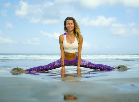 Woman practicing yoga at beautiful beach . Young happy and attractive girl doing flexibility exercise with legs split  on sand in wellness harmony health care and fitness concept