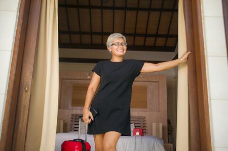 Lifestyle-Porträt einer natürlichen attraktiven und glücklichen asiatischen Frau mittleren Alters in stilvollem Sommerkleid, die zur Balkontür des Hoteleröffnungszimmers ankommt, die begeistert schaut, wie sie einen Reiseurlaub genießt?