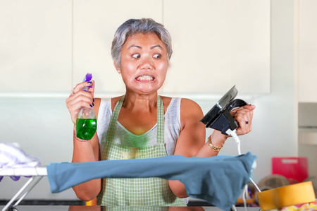 desperate and stressed middle aged Asian woman ironing in stress at home kitchen feeling overwhelmed and tired of working domestic chores in helpless housewife housekeeping concept