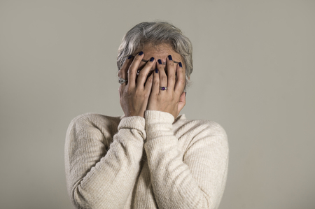 dramatic portrait sad and depressed middle aged woman crying helpless covering face with hands desperate suffering depression problem and anxiety crisis in pain isolated on grey Stock Photo