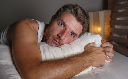close up face portrait of sleepless and awake attractive man with eyes wide open at night lying on bed suffering insomnia sleeping disorder trying to sleep with dramatic facial expression Imagens