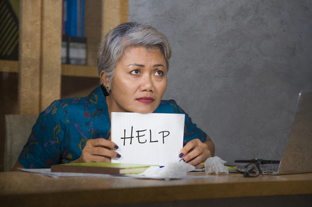 desperate and stressed attractive middle aged Asian woman holding notepad asking for help feeling overworked and exploited working at computer office desk suffering stress and fatigue