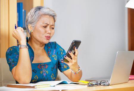 Retrato de estilo de vida de oficina de atractiva mujer asiática de mediana edad preocupada y estresada que usa el teléfono móvil en el escritorio de la computadora portátil que se siente abrumada por el estrés y la expresión de la cara de preocupación Foto de archivo