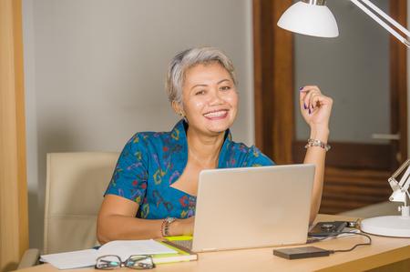 éxito empresarial de la mujer. Retrato de estilo de vida de feliz y atractiva empresaria asiática de mediana edad elegante trabajando sonriendo en el escritorio de la computadora de oficina sintiéndose positivo y exitoso