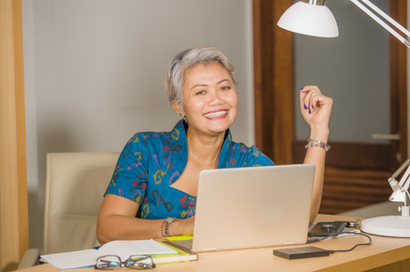 Geschäftserfolg der Frau. Lifestyle-Porträt einer glücklichen und attraktiven, eleganten asiatischen Geschäftsfrau mittleren Alters, die lächelnd am Bürocomputertisch arbeitet und sich positiv und erfolgreich fühlt