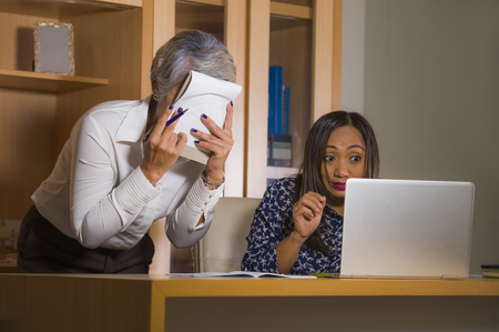 unhappy and upset business woman nagging and scolding on employee girl angry for computer mistake in office boss or chief authority and assistant suffering reprimand concept Stock Photo