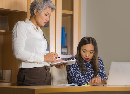 unhappy and upset business woman nagging and scolding on employee girl angry for mistake made by the secretary in boss or chief authority and assistant suffering reprimand concept Stock Photo