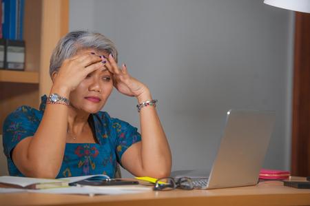 portrait expressif d'une jolie femme asiatique stressée et surmenée travaillant au bureau d'un ordinateur portable dans le stress se sentant frustrée et bouleversée par la pression commerciale et le problème de l'emploi