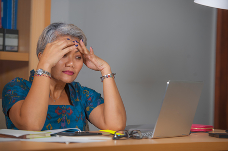 Retrato expresivo de atractiva mujer asiática estresada y con exceso de trabajo que trabaja en el escritorio de la computadora portátil de la oficina en el estrés sintiéndose frustrado y molesto por la presión empresarial y el problema laboral