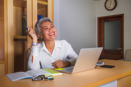corporate job lifestyle portrait of happy and successful attractive middle aged Asian woman working at office laptop computer desk satisfied and efficient in business success