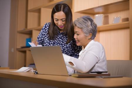 Natürliches Lifestyle-Porträt von zwei Geschäftspartnern oder Arbeitskollegen, die glücklich und fröhlich am Laptop-Computertisch im Büro in weiblicher Zusammenarbeit zusammenarbeiten und arbeiten