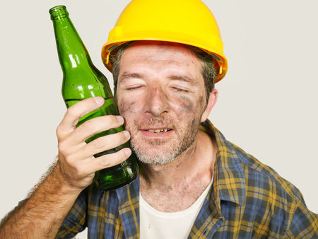 thirsty and tired constructor worker or builder man in safety helmet feeling exhausted holding cold beer bottle against his face refreshing during work break isolated on studio background Archivio Fotografico