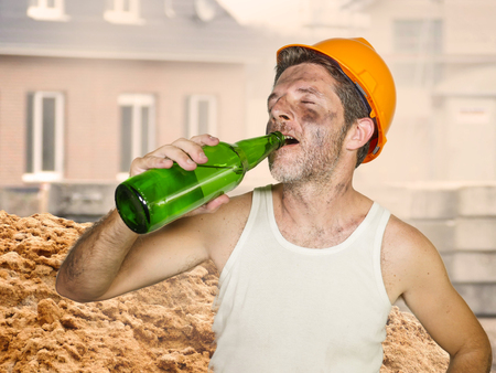 thirsty and tired constructor worker or builder man in safety helmet feeling exhausted drinking cold beer bottle refreshing during work break at building site on a hot Summer day