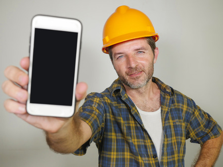 corporate job portrait of constructor worker in contractor helmet holding mobile phone offering company building and repair services smiling cheerful and confident inviting for calling