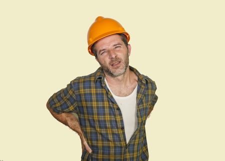 verärgerter und erschöpfter Bauarbeiter oder Reparaturmann mit Bauhelm, der sich über Schmerzen im unteren Rücken beschwert, nachdem er hart auf ebenem Hintergrund gearbeitet hat Standard-Bild