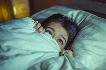 jonge, slapeloze, mooie en bange Aziatische Chinese vrouw die 's nachts wakker op bed ligt en aan nachtmerrie lijdt na het kijken naar zombie-horrorfilm in angst en gestresste gezichtsuitdrukking Stockfoto