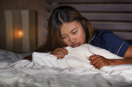 dramatic lifestyle portrait of young attractive sad and depressed Asian woman in pajamas lying in bed in pain suffering depression and anxiety feeling lonely and desperate after break up relationship