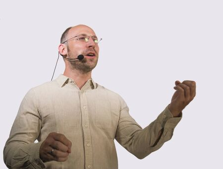 happy attractive and confident businessman speaker with headset giving coaching conference training for business success smiling cheerful and positive in casual shirt isolated on studio background