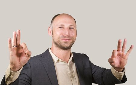 corporate company isolated portrait of young attractive and successful businessman smiling happy and confident isolated white background giving ok hand sign entrepreneur business success
