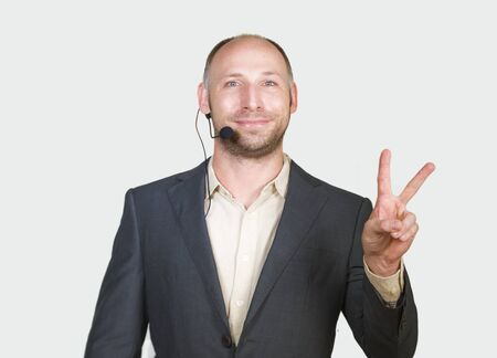 isolated corporate portrait of young attractive and successful businessman smiling happy and confident isolated white background giving victory fingers sign entrepreneur business success