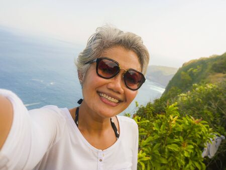 middle age 50s happy and cheerful Asian woman with grey hair taking selfie with mobile phone at beautiful tropical beach island smiling at cliff viewpoint enjoying Summer holidays travel destination Stock fotó