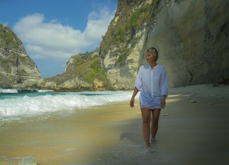 holidays lifestyle portrait of happy and relaxed Asian mature woman on her 50s with grey hair walking at tropical paradise desert beach under a Summer blue sky enjoying tourist travel destination