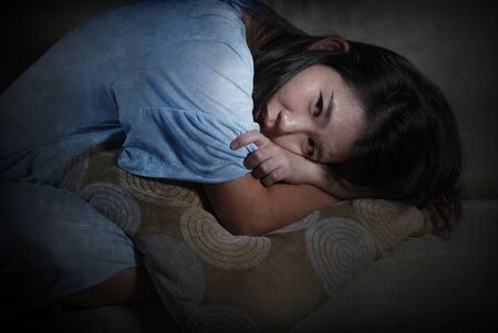 dramatic lifestyle portrait of young desperate sad and depressed Asian Korean woman sitting at home sofa couch suffering depression problem and anxiety crisis feeling lonely and helpless Stock Photo