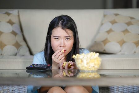 young beautiful and relaxed Asian Japanese woman watching Korean drama on television on sad romantic movie eating popcorn at home living room couch concentrated and mesmerized Standard-Bild
