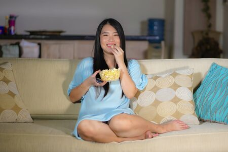 young happy and excited Asian Korean woman with TV remote controller eating popcorn bowl watching television enjoying Korean drama or comedy movie having fun relaxed and cheerful
