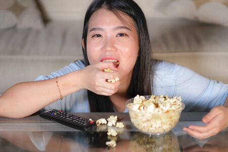 young happy and excited Asian Japanese woman with TV remote controller eating popcorn bowl watching television enjoying Korean drama or comedy movie having fun relaxed and cheerful