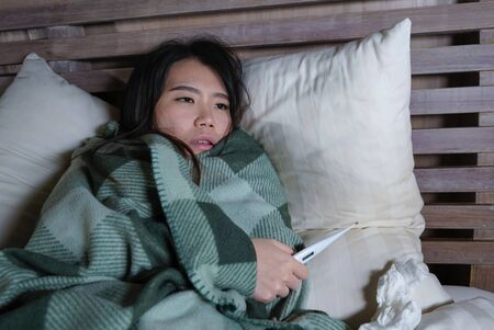 lifestyle portrait of young beautiful sick and exhausted Asian Japanese woman suffering cold and flu holding thermometer having temperature lying on bed covering with blanket feeling ill and unwell