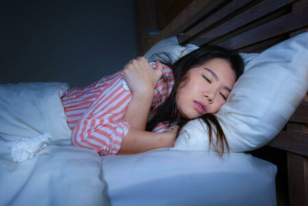 young beautiful sad and depressed Asian Chinese woman trembling in bed suffering cold and flu at night feeling unwell at night in her bedroom in health care and depression problem concept