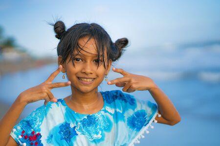 vacances plage mode de vie portrait d'une jeune fille asiatique belle et heureuse de 8 ou 9 ans avec une jolie coiffure à double pain jouant sans soucis dans la mer profitant des vacances d'été en s'amusant seul