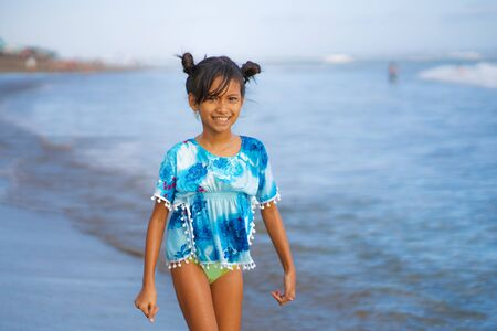 holiday beach lifestyle portrait of young beautiful and happy Asian child girl 8 or 9 years old with cute double buns hair style playing carefree in the sea enjoying Summer vacation having fun alone