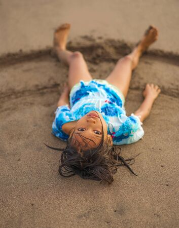 beach lifestyle portrait of young beautiful and happy Asian American mixed ethnicity child girl 7 or 8 years old playing lying on the sand having fun enjoying Summer holidays 스톡 콘텐츠