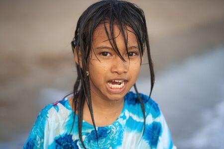 portrait de mode de vie sur la plage d'une jeune fille belle et heureuse de 7 ou 8 ans d'origine asiatique aux cheveux mouillés profitant de vacances jouant dans la mer s'amusant avec l'eau sans soucis Banque d'images