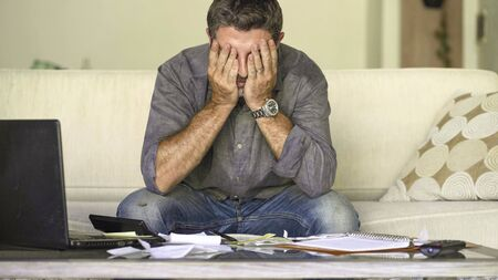 young stressed and desperate man at home living room couch doing domestic accounting with paperwork and calculator feeling overwhelmed and worried suffering financial crisis debt and ruin Stok Fotoğraf