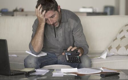 young stressed and desperate man at home living room couch doing domestic accounting with paperwork and calculator feeling overwhelmed and worried suffering financial crisis debt and ruin